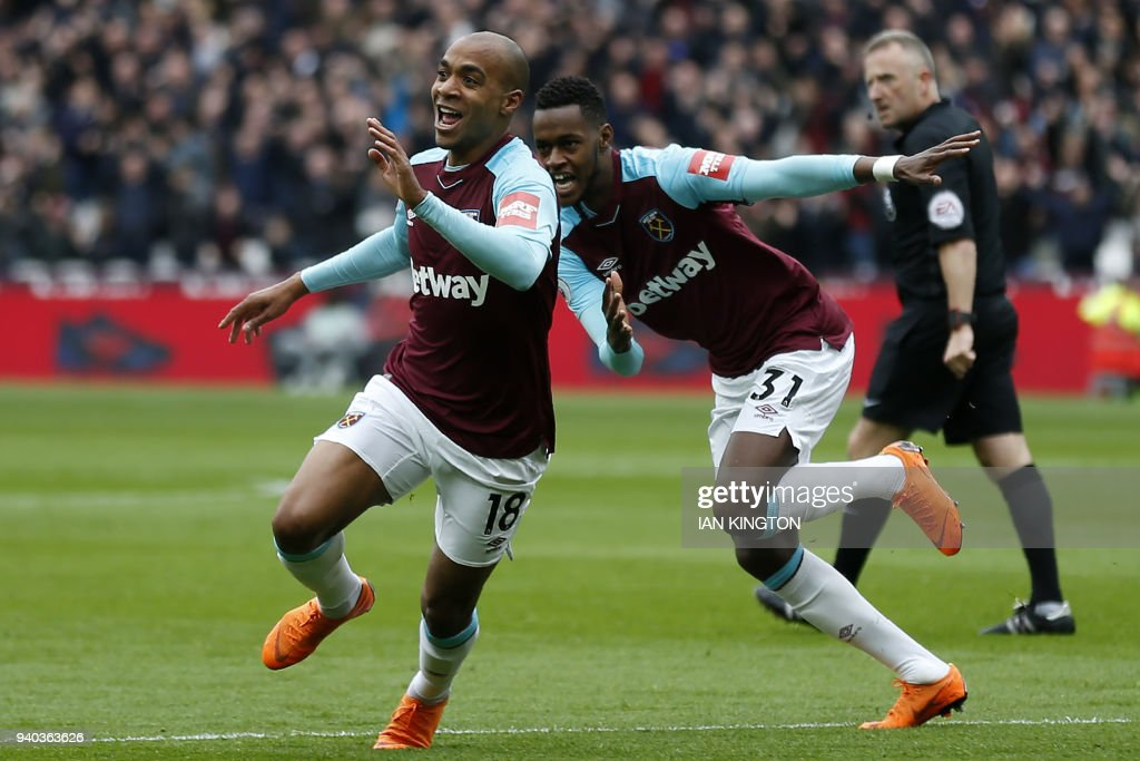 West Ham United's Portuguese midfielder Joao Mario (L) celebrates with West Ham United's Swiss midfielder Edimilson Fernandes after scoring the opening goal of the English Premier League football match between West Ham United and Southampton at The London Stadium, in east London on March 31, 2018. / AFP PHOTO / Ian KINGTON / RESTRICTED TO EDITORIAL USE. No use with unauthorized audio, video, data, fixture lists, club/league logos or 'live' services. Online in-match use limited to 75 images, no video emulation. No use in betting, games or single club/league/player publications. /