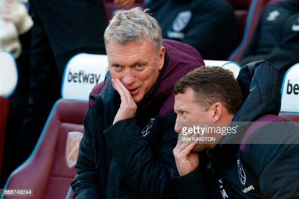 West Ham United's Scottish manager David Moyes chats with his assistant Billy McKinlay before kick off in the English Premier League football match...