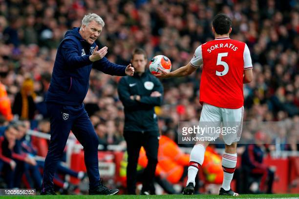 West Ham United's Scottish manager David Moyes gestures on the touchline to Arsenal's Greek defender Sokratis Papastathopoulos during the English...