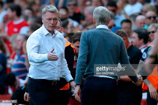 West Ham United's Scottish manager David Moyes offers his hand to Arsenal's French manager Arsene Wenger at the end of the English Premier League...