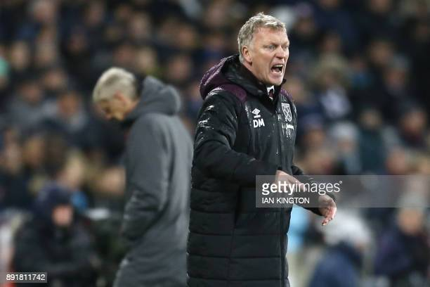 West Ham United's Scottish manager David Moyes reacts as Arsenal's French manager Arsene Wenger returns to the dugout during the English Premier...