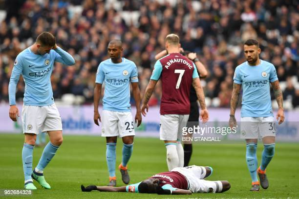 West Ham United's Senegalese midfielder Cheikhou Kouyate lies injured during the English Premier League football match between West Ham United and...