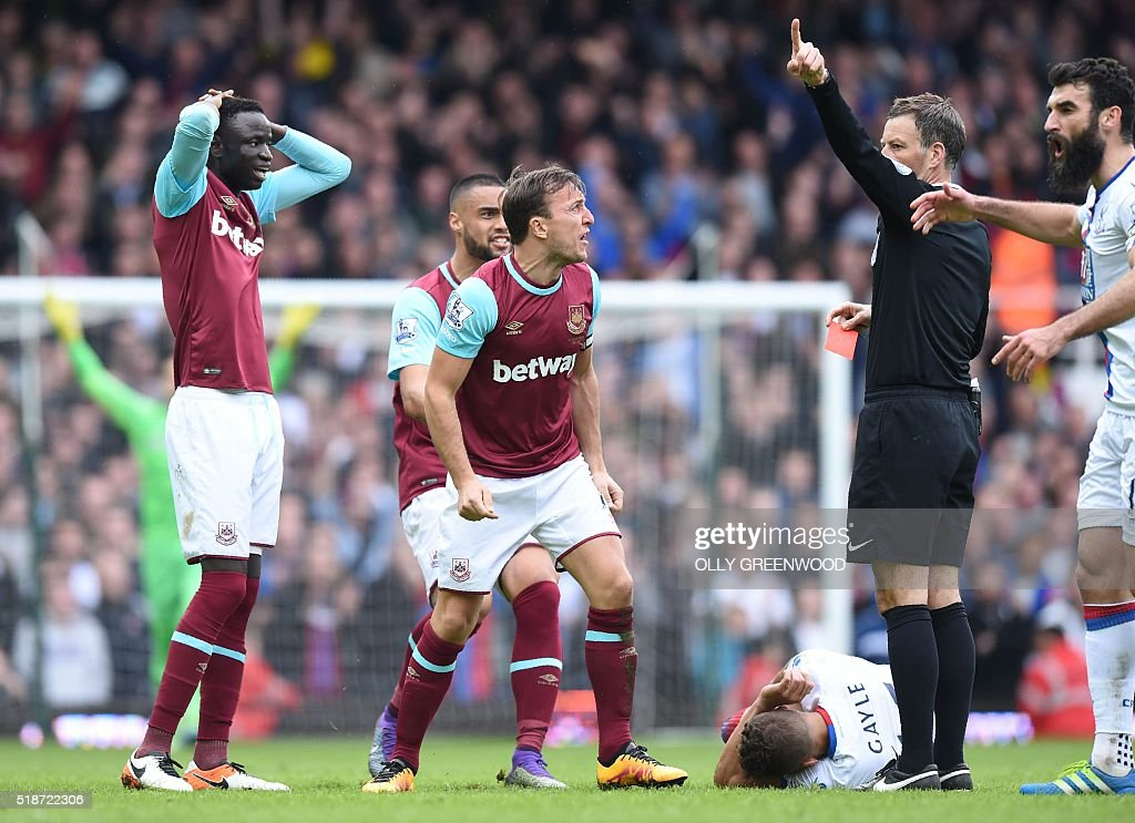 West Ham United's Senegalese midfielder Cheikhou Kouyate (L) reacts after being sent off by referee Mark Clattenburg (2nd R) during the English Premier League football match between West Ham United and Crystal Palace at The Boleyn Ground in Upton Park, in east London on April 2, 2016. The game finished 2-2. / AFP / OLLY GREENWOOD / RESTRICTED TO EDITORIAL USE. No use with unauthorized audio, video, data, fixture lists, club/league logos or 'live' services. Online in-match use limited to 75 images, no video emulation. No use in betting, games or single club/league/player publications. /