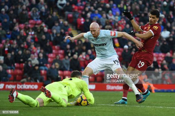 West Ham United's Spanish goalkeeper Adrian saves from Liverpool's English striker Dominic Solanke defended by West Ham United's Welsh defender James...
