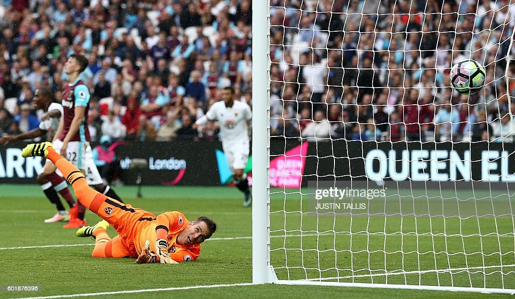 West Ham United's Spanish goalkeeper Adrian watches as the ball, shot by Watford's German-born Greek midfielder José Holebas (unseen) enters his net, to score his West Ham's fourth goal during the English Premier League football match between West Ham United and Watford at The London Stadium, in east London on September 10, 2016. / AFP / JUSTIN TALLIS / RESTRICTED TO EDITORIAL USE. No use with unauthorized audio, video, data, fixture lists, club/league logos or 'live' services. Online in-match use limited to 75 images, no video emulation. No use in betting, games or single club/league/player publications. /