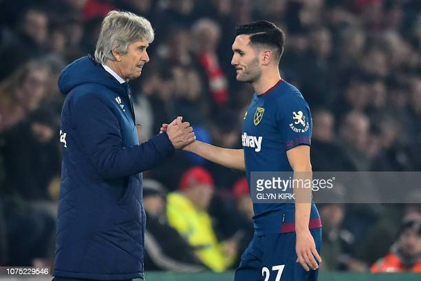West Ham United's Spanish striker Lucas Perez shakes hands with West Ham United's Chilean manager Manuel Pellegrini as he leaves the pitch...