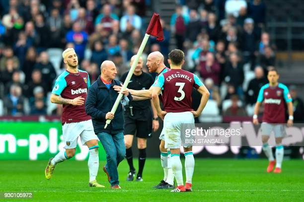 West Ham United's Welsh defender James Collins confronts a pitch invader carrying a corner flag during the English Premier League football match...