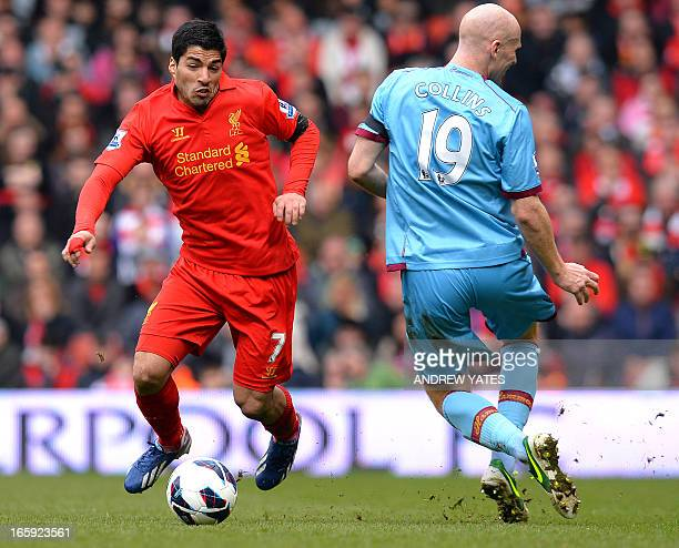 West Ham United's Welsh defender James Collins vies with Liverpool's Uruguayan forward Luis Suarez at Anfield stadium in Liverpool, northwest...