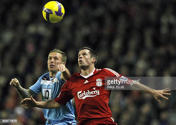 West Ham United's Welsh forward Craig Bellamy challenges Liverpool's English defender Jamie Carragher during their English Premier League football...
