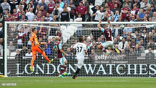 West Ham United's Winston Reid is unable to stop Watford's Troy Deeney's shot for his sides second goal during the Premier League match between West...