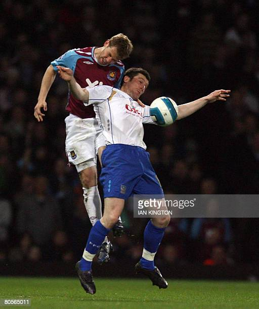 West Ham's American footballer Jonathan Spector heads the ball away from David Nugent of Portsmouth during a Barclays Premiership game at Upton Park...