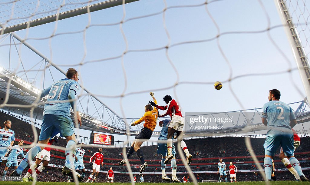 West Ham's goalkeeper Rob Green (centre L) punches the ball out under a challenge from Arsenal's Togolese player Emmanuel Adebayor (centre R) during the Premiership match at The Emirates Stadium in London on January 31, 2009. The game ended 0-0. AFP PHOTO / Adrian Dennis FOR EDITORIAL USE ONLY Additional licence required for any commercial/promotional use or use on TV or internet (except identical online version of newspaper) of Premier League/Football League photos. Tel DataCo +44 207 2981656. Do not alter/modify photo.