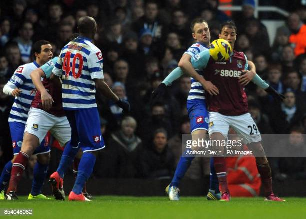 West Ham's Marouane Chamakh appears to be held back by QPR's Clint Hill during the Barclays Premier League match at Upton Park London