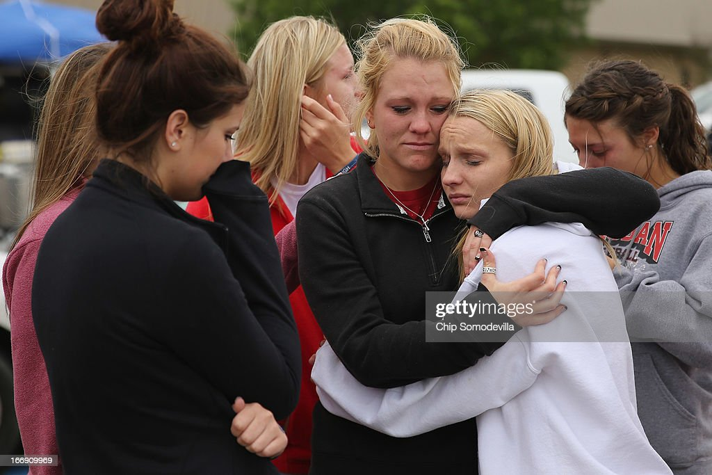 West High School senior students Kelsey Hoelscher (C) and Heather Perry (R) embrace after praying for the victims and survivors the day after the West Fertilizer Company explosion April 18, 2013 in West, Texas. Hoelscher's uncles, Bob Snokhous and Doug Snokhous, were volunteer fire fighters who are presumed dead after the fertilizer company caught fire and exploded, injuring more than 160 people and leaving damaged buildings for blocks in every direction.