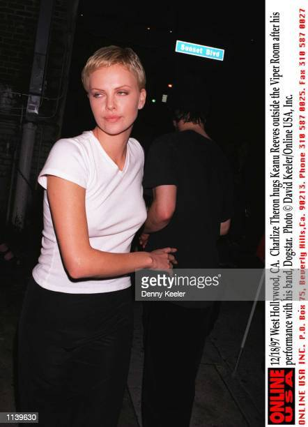 West Hollywood, CA. Charlize Theron hugs Keanu Reeves outside the Viper Room after his performance with his band, Dogstar.