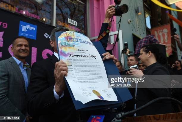 West Hollywood from Mayor John Duran displays a proclamation during a ceremony honoring adult film star Stormy Daniels May 23 2018 in West Hollywood...