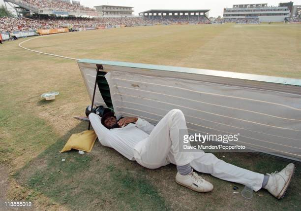 West Indian bowler Courtney Walsh lies on the ground behind an advertising board on the field boundary during the 4th Test match against the West...