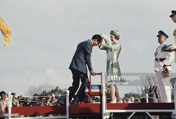 West Indian cricketer Garfield Sobers receives a knighthood from Queen Elizabeth II during her visit to Barbados, February 1975.