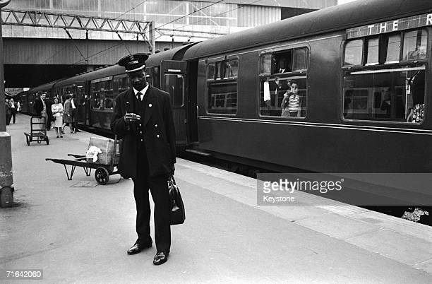 West Indian guard Asquith Xavier on his first day at work at Euston Station, London, 15th August 1966. Xavier is the first black guard to work at the...