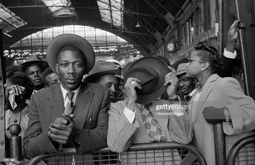 West Indian immigrants arrive at Victoria Station, London, after their journey from Southampton Docks. Original Publication: Picture Post - 8405 - Thirty Thousand Colour Problems - pub. 1956