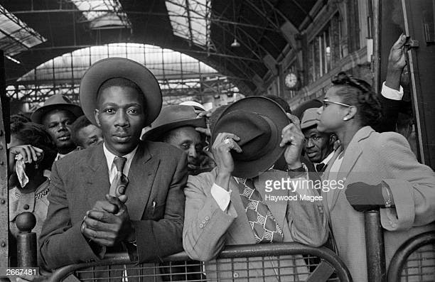 West Indian immigrants arrive at Victoria Station, London, after their journey from Southampton Docks. Original Publication: Picture Post - 8405 -...