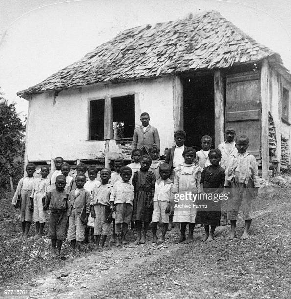 West Indian school children and teachers before a rural school house in Jamaica