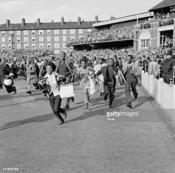 West Indian spectators run across the Oval ground in London, following the West Indies victory in the final test match, 26th August 1963.