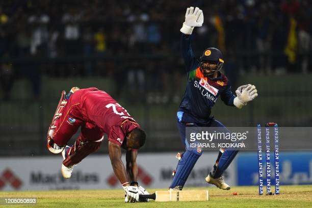 West Indies' Andre Russell dives to reach the crease as Sri Lanka's wicketkeeper Kusal Perera watches during the first Twenty20 international cricket...