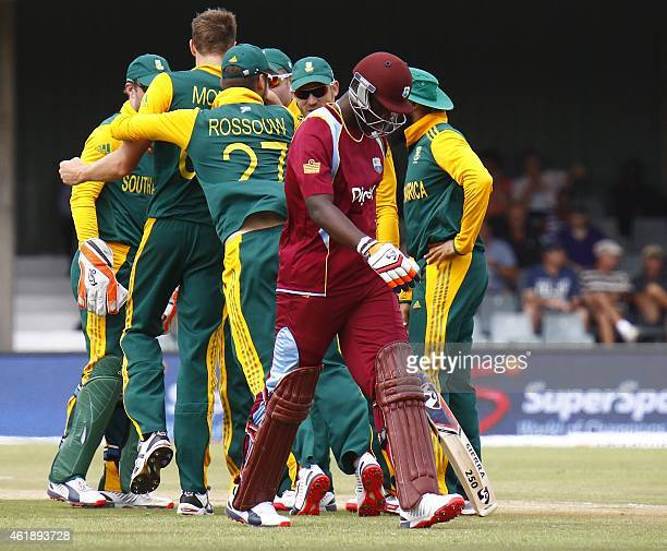 West Indies batsman Andre Russel walks off the field as South Africa players celebrates his wicket during the third One Day International at East...