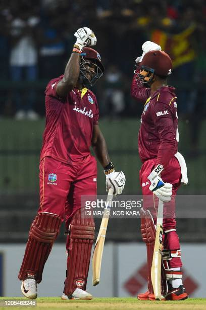 West Indies' batsman Andre Russell and Shimron Hetmyer celebrate after scoring the winning run to defeat Sri Lanka by seven wickets during the second...