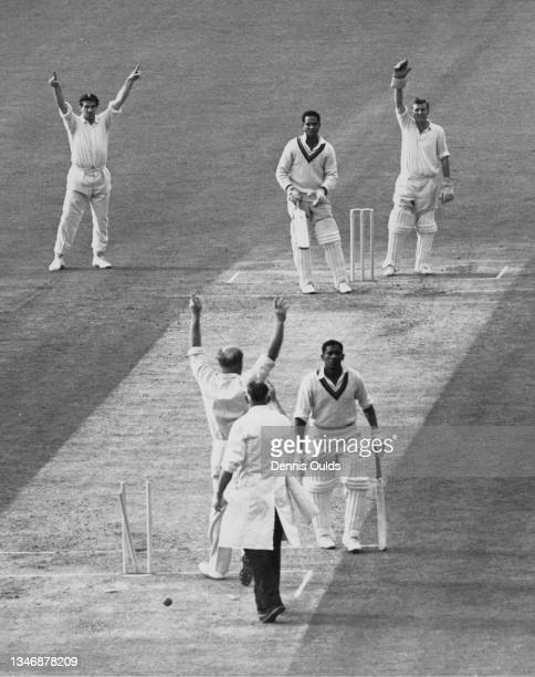 West Indies batsman Basil Butcher walks from the wicket after being run out by England bowler Tony Lock after Garfield Sobers played a drive that...