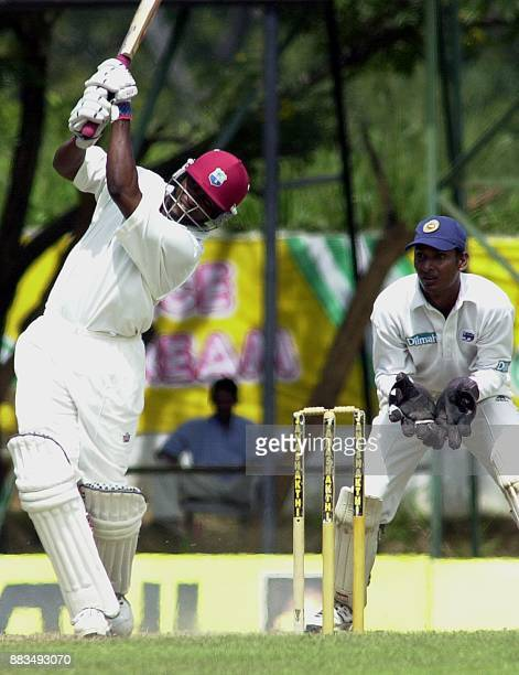 West Indies batsman Brian Lara bats for six as Sri lankan wicketkeeper Kumar Sangakkara looks on during the fourth day of the second cricket test...