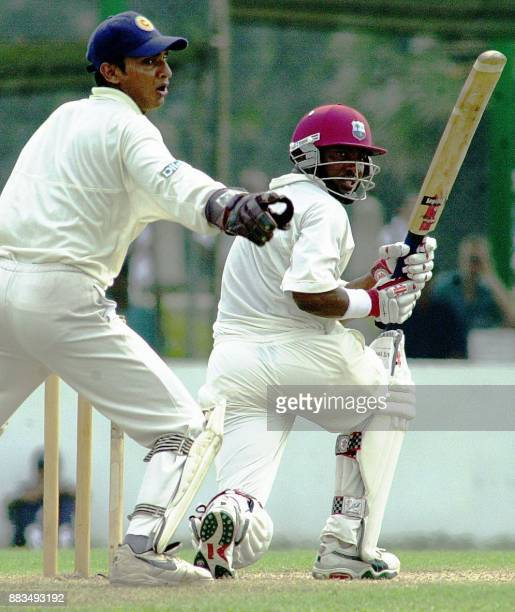 West Indies batsman Brian Lara hits a ball as Sri Lankan wicketkeeper Kumar Sangakkara looks on during the first day of the first cricket test match...