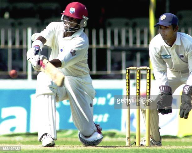 West Indies batsman Brian Lara hits a ball to the boundary for four as Sri Lankan wicketkeeper Kumar Sangakkara looks on during the first day of the...