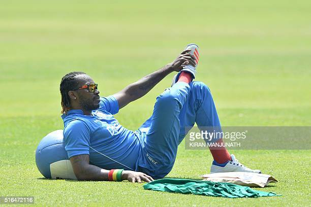 West Indies batsman Chris Gayle stretches during a practice session at The Chinnaswamy Stadium in Bangalore on March 19 ahead of their World T20...