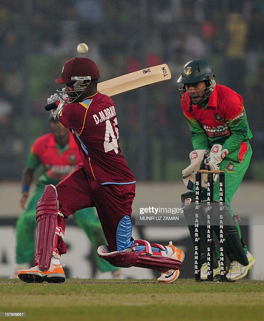 West Indies batsman Darren Bravo (L) plays a shot as Bangladesh captain Mushfiqur Rahim looks on during the fifth one day international between Bangladesh and West Indies at The Sher-e-Bangla Natio...