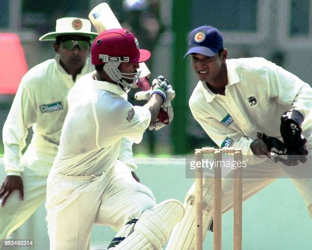 West Indies batsman Darren Ganga hits a ball as Sri Lankan wicketkeeper Kumar Sangakkara and fielder Mahela Jayawardena look on during the first day...