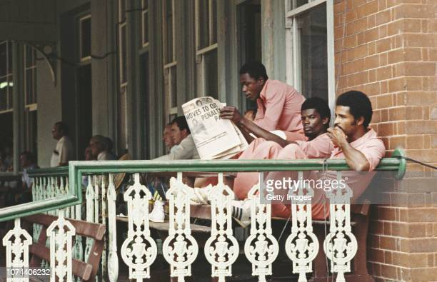 West Indies batsman Desmond Haynes reads a paper as Albert Padmore looks on from the players balcony in their pink kit during the World Series of...