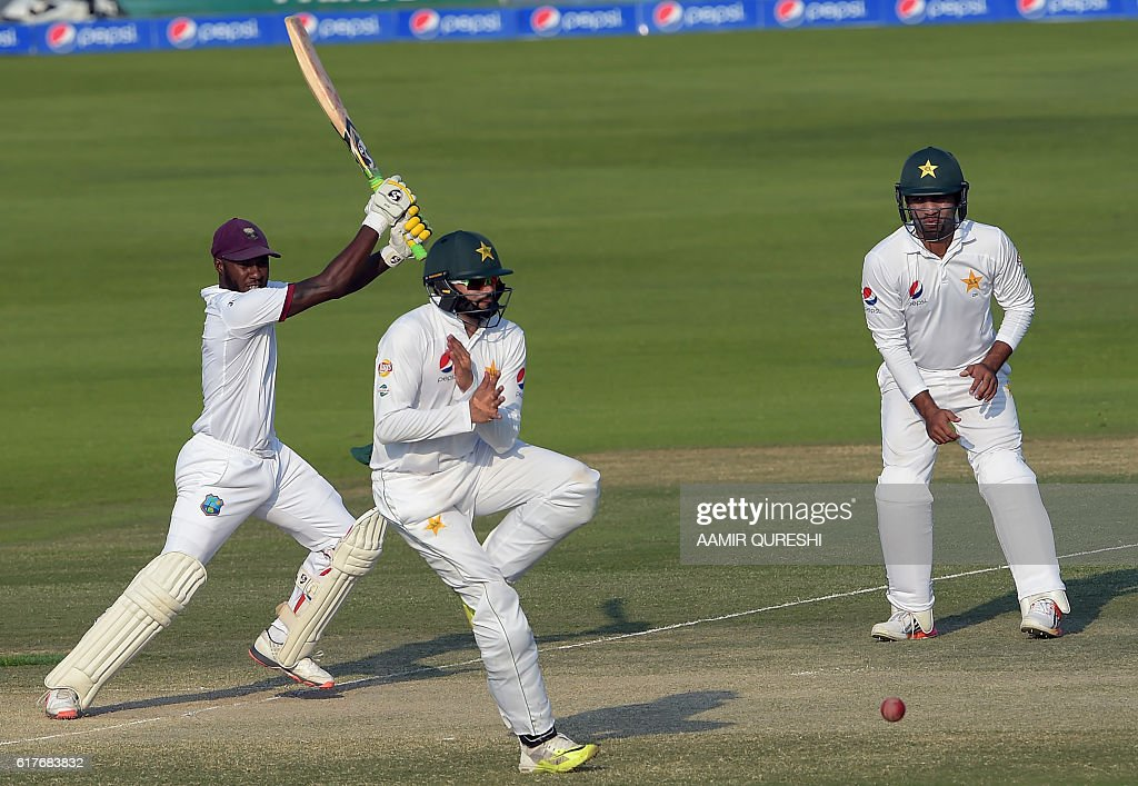 West Indies' batsman Jermaine Blackwood (L) plays a shot as Pakistani cricketer Azhar Ali (C) avoids the ball while teammate Sami Aslam looks on during the fourth day of the second Test between Pakistan and the West Indies at the Sheikh Zayed Cricket Stadium in Abu Dhabi on October 24, 2016. Pakistan set West Indies a target of 456 runs to win the second Test after declaring their second innings at 227-2 on the fourth day in Abu Dhabi. / AFP / AAMIR