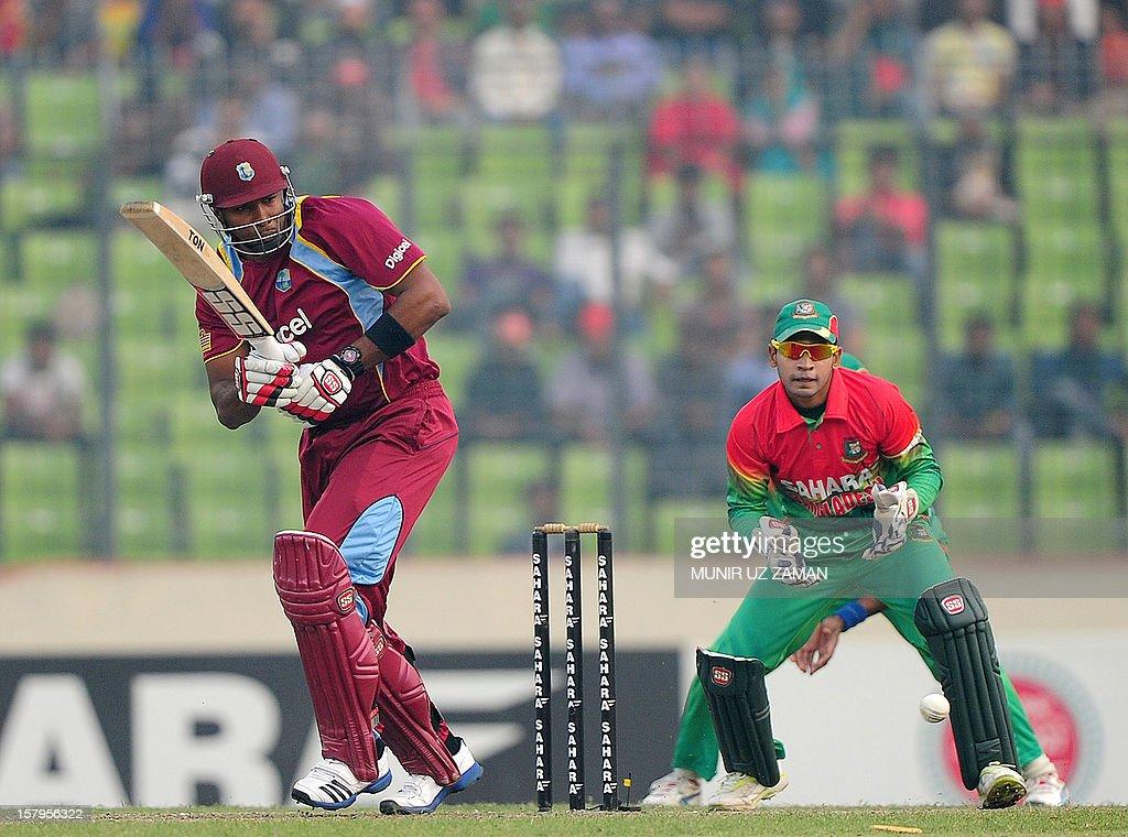 West Indies batsman Kieron Pollard (L) plays a shot as Bangladesh captain Mushfiqur Rahim looks on during the fifth one day international between Bangladesh and West Indies at The Sher-e-Bangla National Cricket Stadium in Dhaka on December 8, 2012. AFP PHOTO/ Munir uz ZAMAN