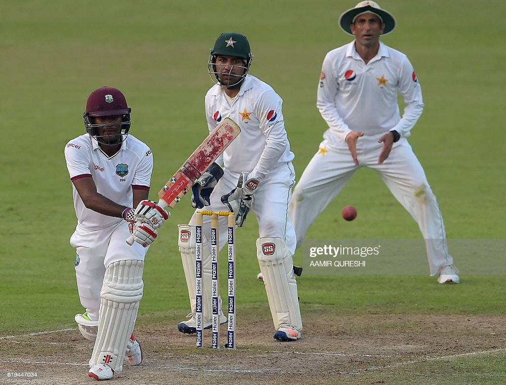 West Indies' batsman Kraigg Brathwaite (L) plays a shot as Pakistani wicketkeeper Sarfraz Ahmed (C) and teammate Younis Khan look on during the second day of the third and final Test between Pakistan and the West Indies at the Sharjah Cricket Stadium in Sharjah on October 31, 2016. Pakistan, resuming at 255-8, were dismissed for 281 in their first innings on the second day of the third and final Test against West Indies in Sharjah. / AFP / AAMIR