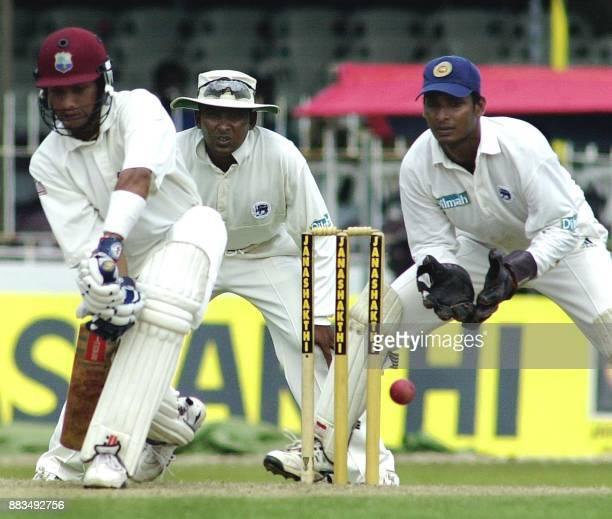 West Indies batsman Ramnaresh Sarwan hits a ball as Sri Lankan wicketkeeper Kumar Sangakkara and fielder Mahela Jayawardane look on during the first...