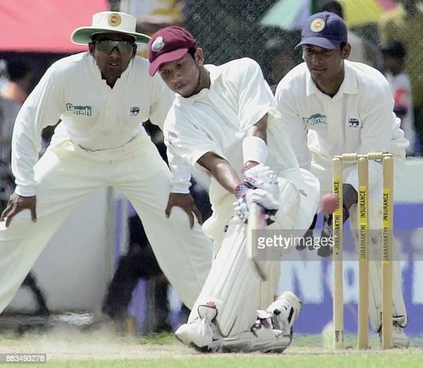 West Indies batsman Ramnaresh Sarwan sweeps a ball as Sri Lankan fielder Mahela Jayawardena and wicketkeeper Kumar Sangakkara looks on during the...