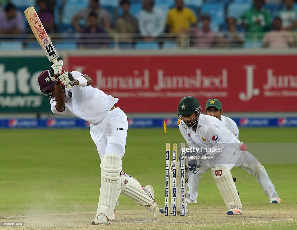 West Indies batsman Roston Chase (L) is bowled out by Pakistani spinner Yasir Shah (unseen) on the final day of the first day-night Test between Pakistan and the West Indies at the Dubai International Cricket Stadium in the Gulf Emirate on October 17, 2016. / AFP / AAMIR