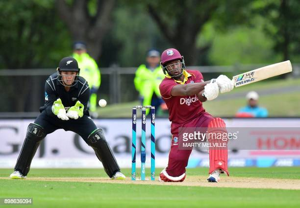 West Indies batsman Rovman Powell bats as New Zealand's wicket keeper Tom Latham looks on during the third oneday international cricket match between...