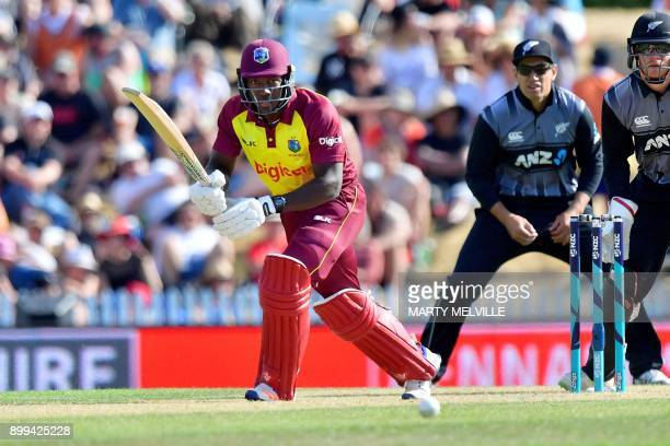 West Indies batsman Rovman Powell plays a shot as New Zealand's Ross Taylor and wicketkeeper Glenn Phillips look on during the first Twenty20...
