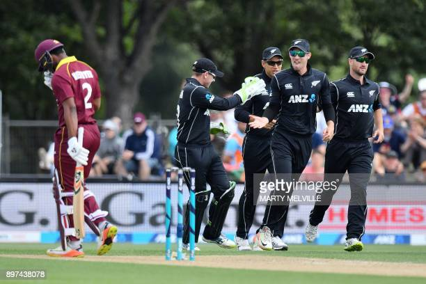 West Indies batsman Shimron Hetmyer walks off the pitch after being dismissed as New Zealand players celebrate during the second oneday international...