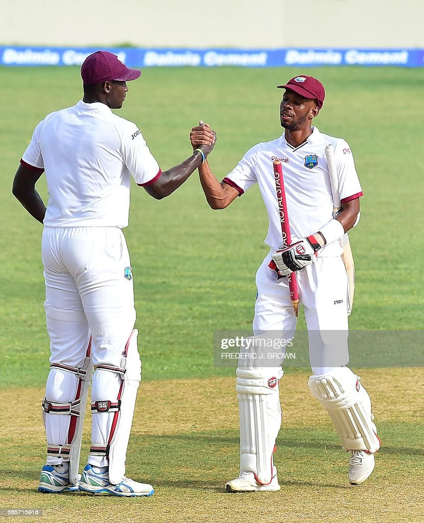 West Indies batsmen Jason Holder (L) and Roston Chase congratulate one another at the end of their match on day five of their Second Test cricket match on August 3, 2016 at Sabina Park in Kingston, Jamaica which ended in a draw. / AFP / Frederic J. BROWN