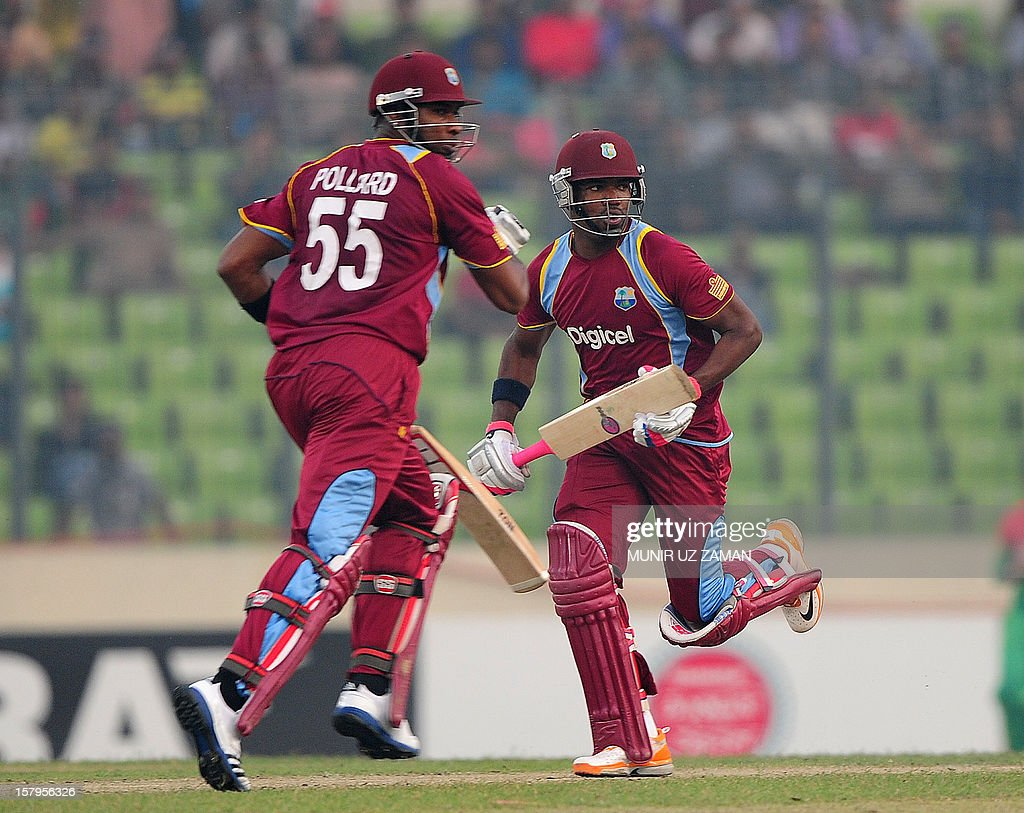 West Indies batsmen Kieron Pollard (L) and Darren Bravo run between the wickets during the fifth one day international between Bangladesh and West Indies at The Sher-e-Bangla National Cricket Stadi...