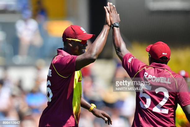 West Indies bowler Carlos Brathwaite celebrates with teammate Rovman Powell after catching New Zealand's Colin Munro during the first Twenty20...